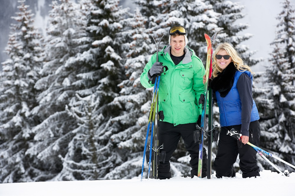 Couples smiling with ski equipments