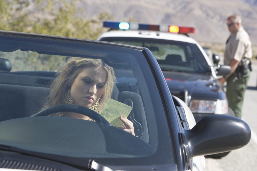 police officer issuing ticket on a driver