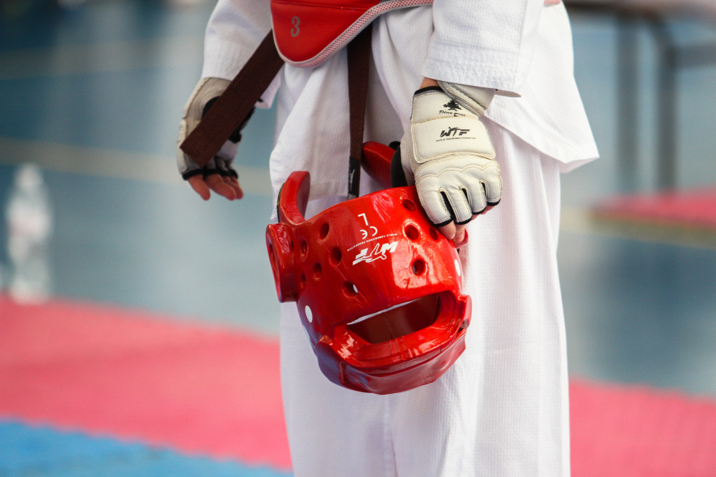a red helmet for taekwondo, held by an athlete